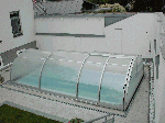 Swimming pool cover (closed) with demountable front wall and side boarding door