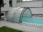 Swimming pool cover (open) with demountable front wall and side boarding door